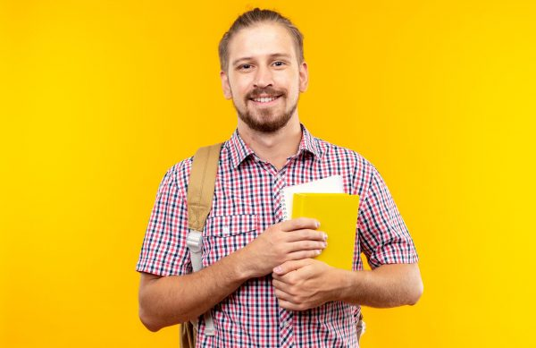 pleased-looking-camera-young-guy-student-wearing-backpack-holding-book-isolated-orange-wall (1)